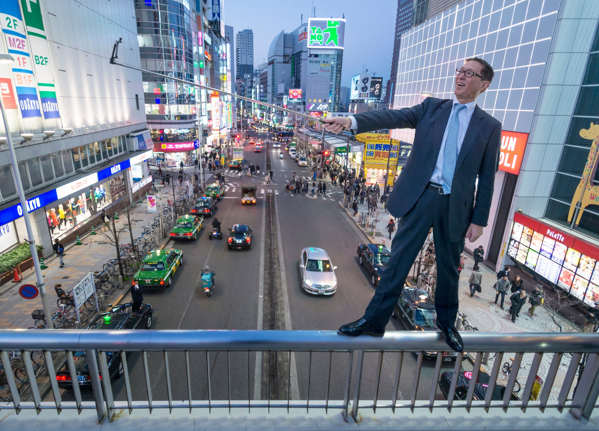 Japanese businessman with smartphone in Tokyo at dusk.