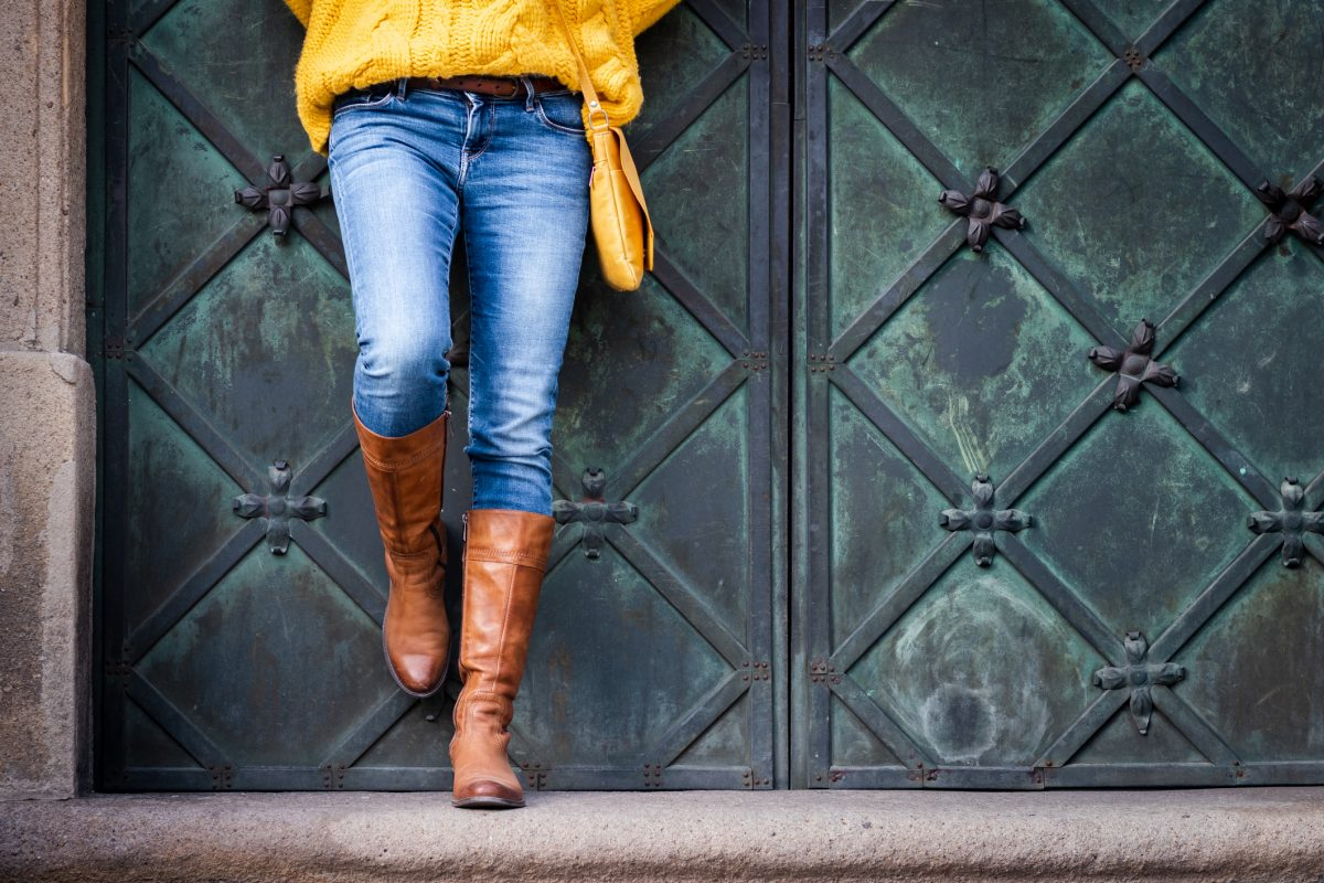 A woman wearing jeans, knitted sweater and leather boots is leaning at an ancient gate.