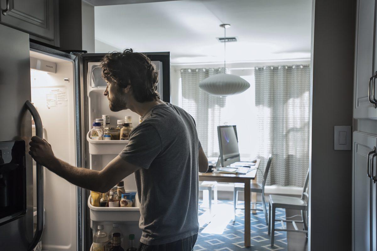man checking fridge