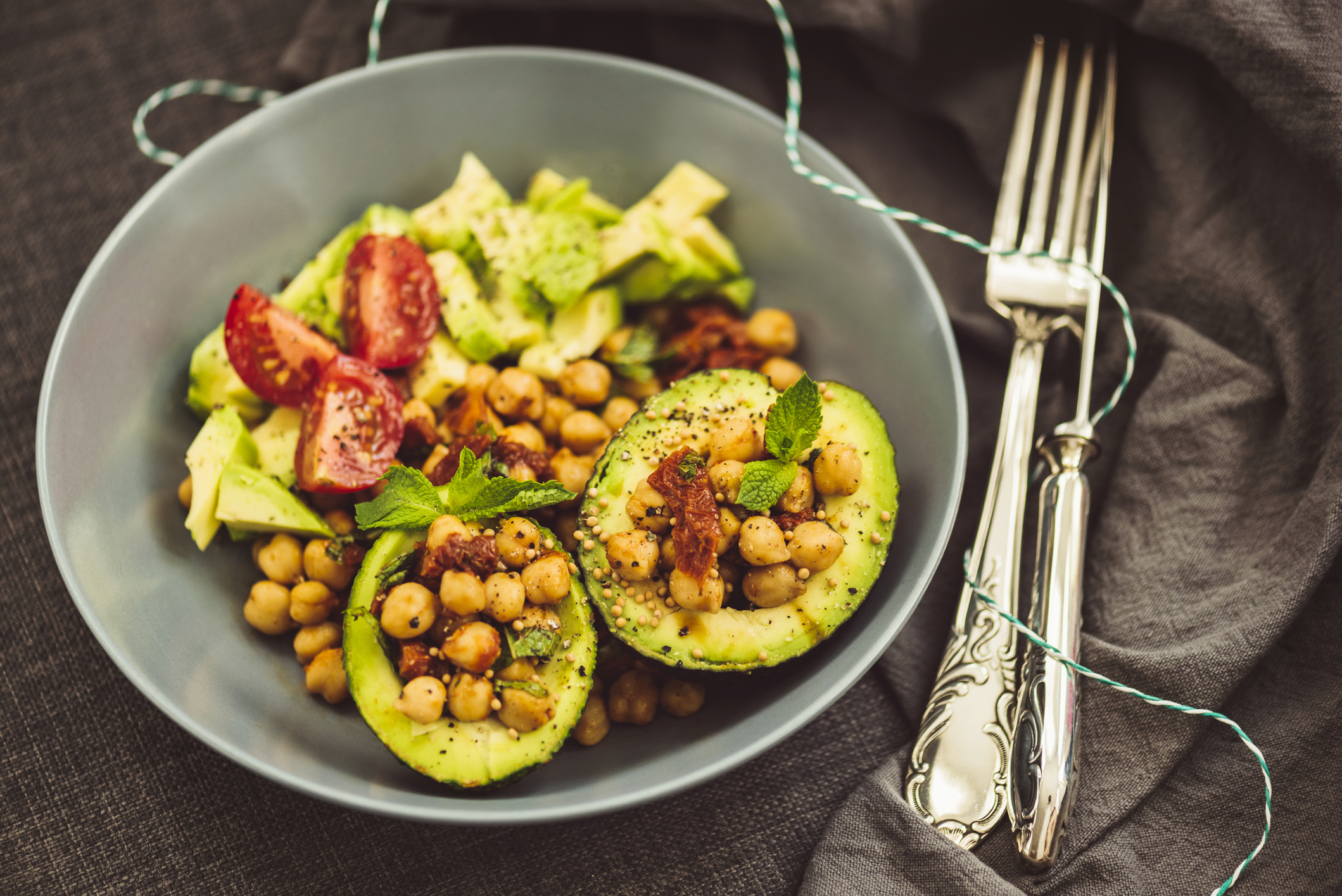 Superfood Salad with Avocado, Chickpeas and Dried Tomato decorated with mint leaves and grains of mustard seed