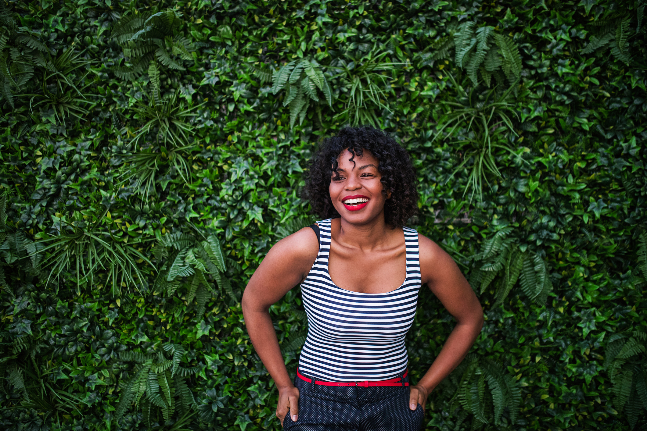 A portrait of a black laughing woman standing against green background of bush leaves.