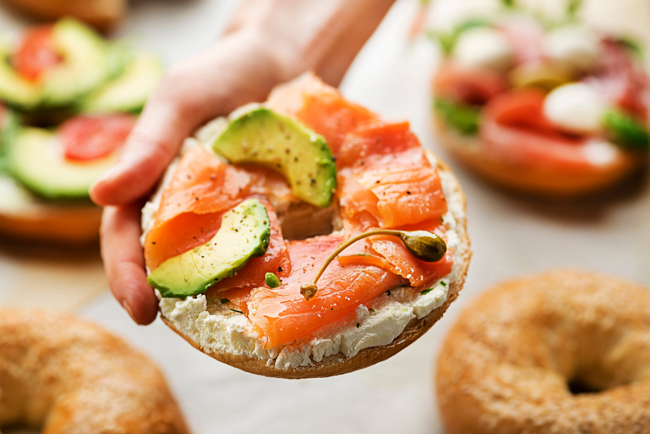 Woman is holding a Bagel with cream, avocado and smoked salmon oHealthy breakfast food.