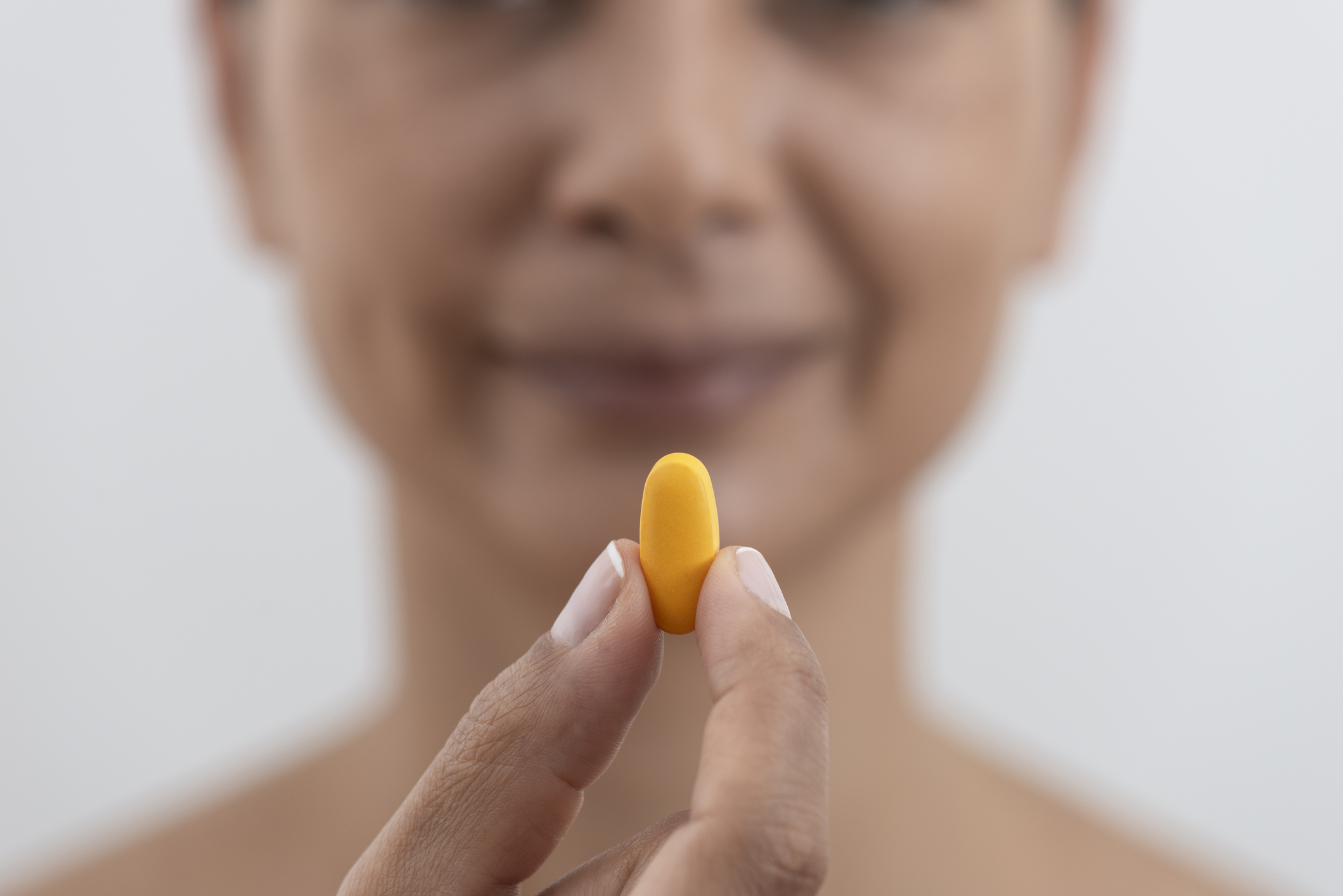 Woman showing pill.