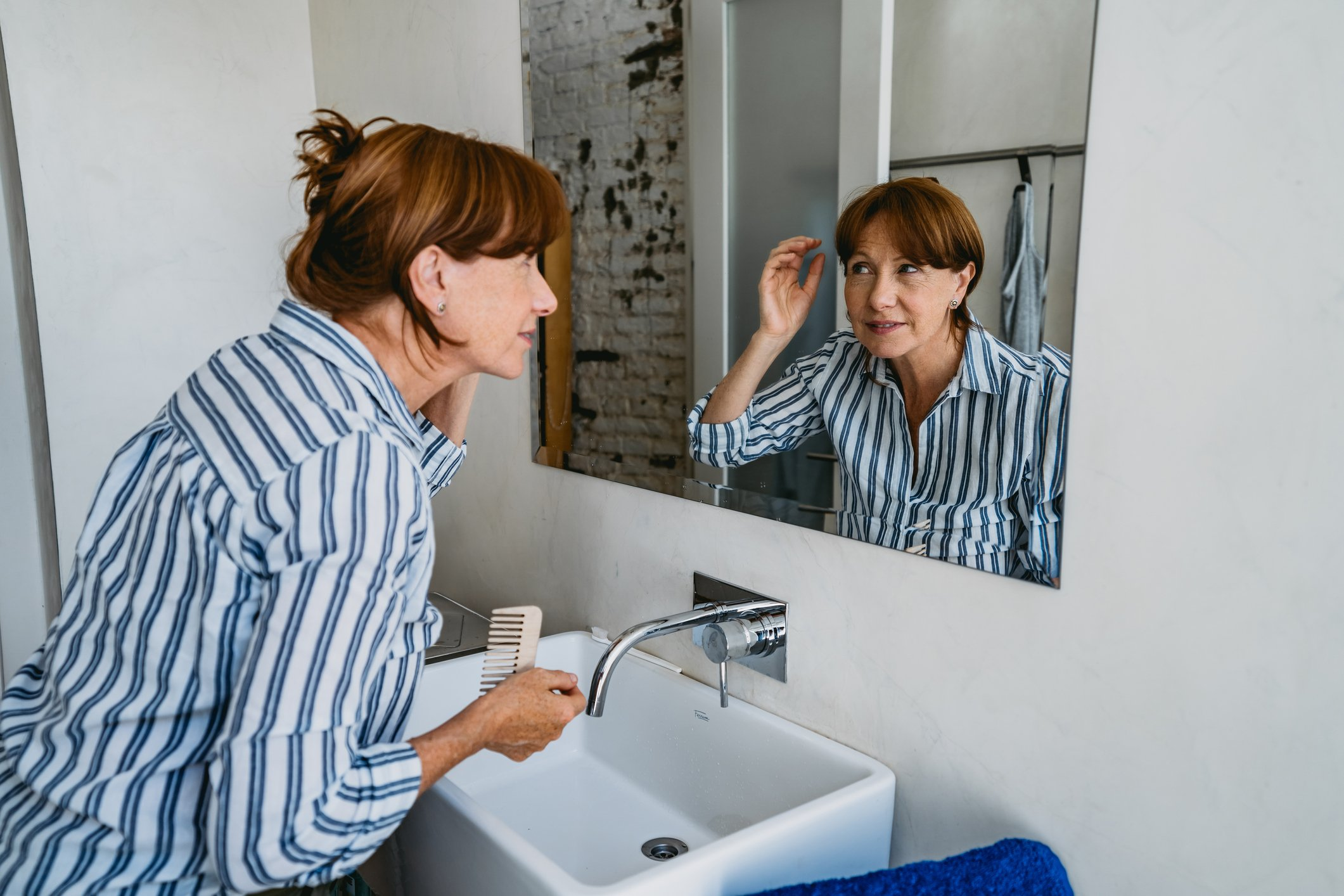 Senior woman adjusting her hair in front of a mirror in bathroom.