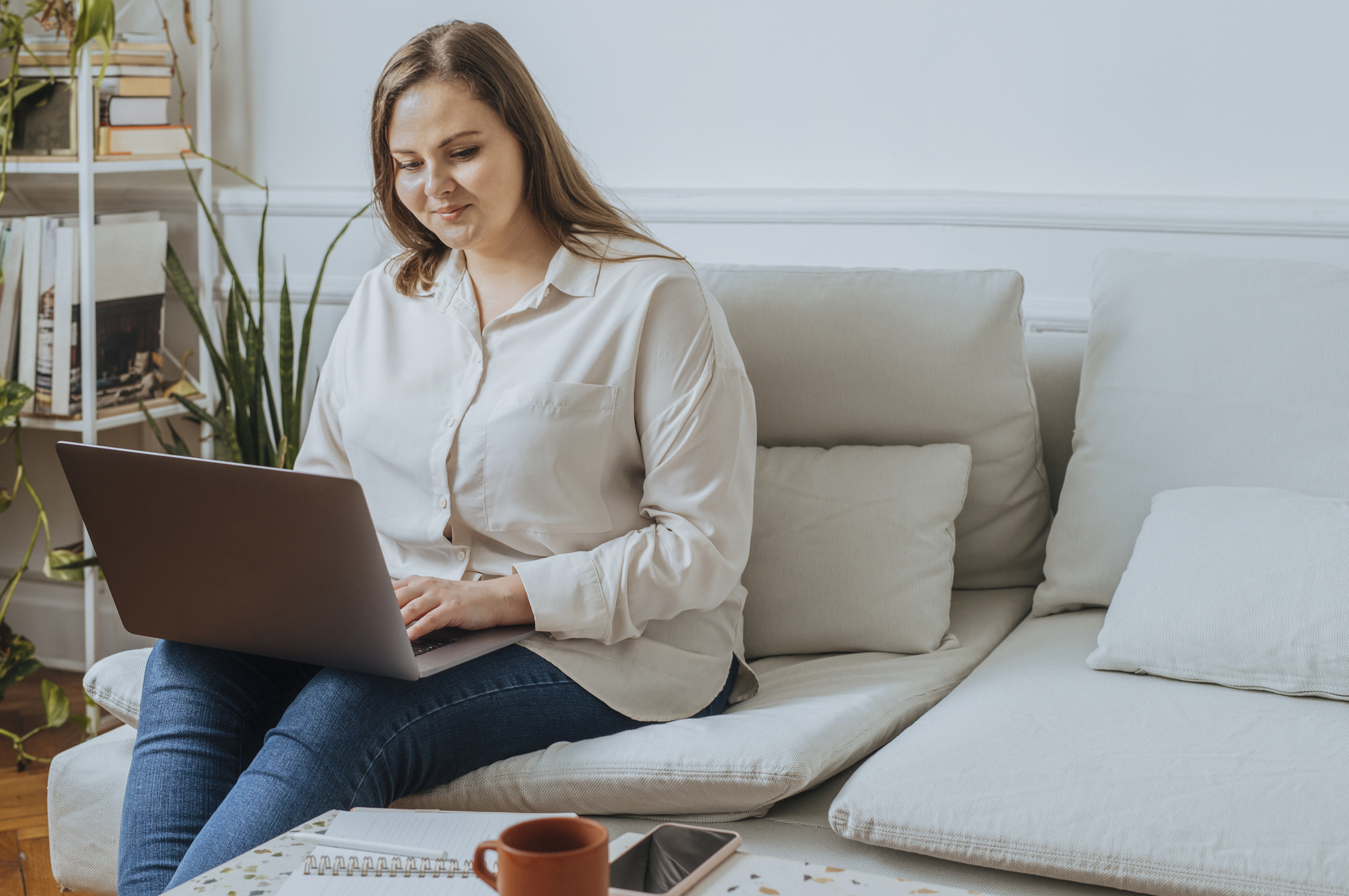 Smiling Caucasian businesswoman sitting on a sofa and working on her laptop in the living room.