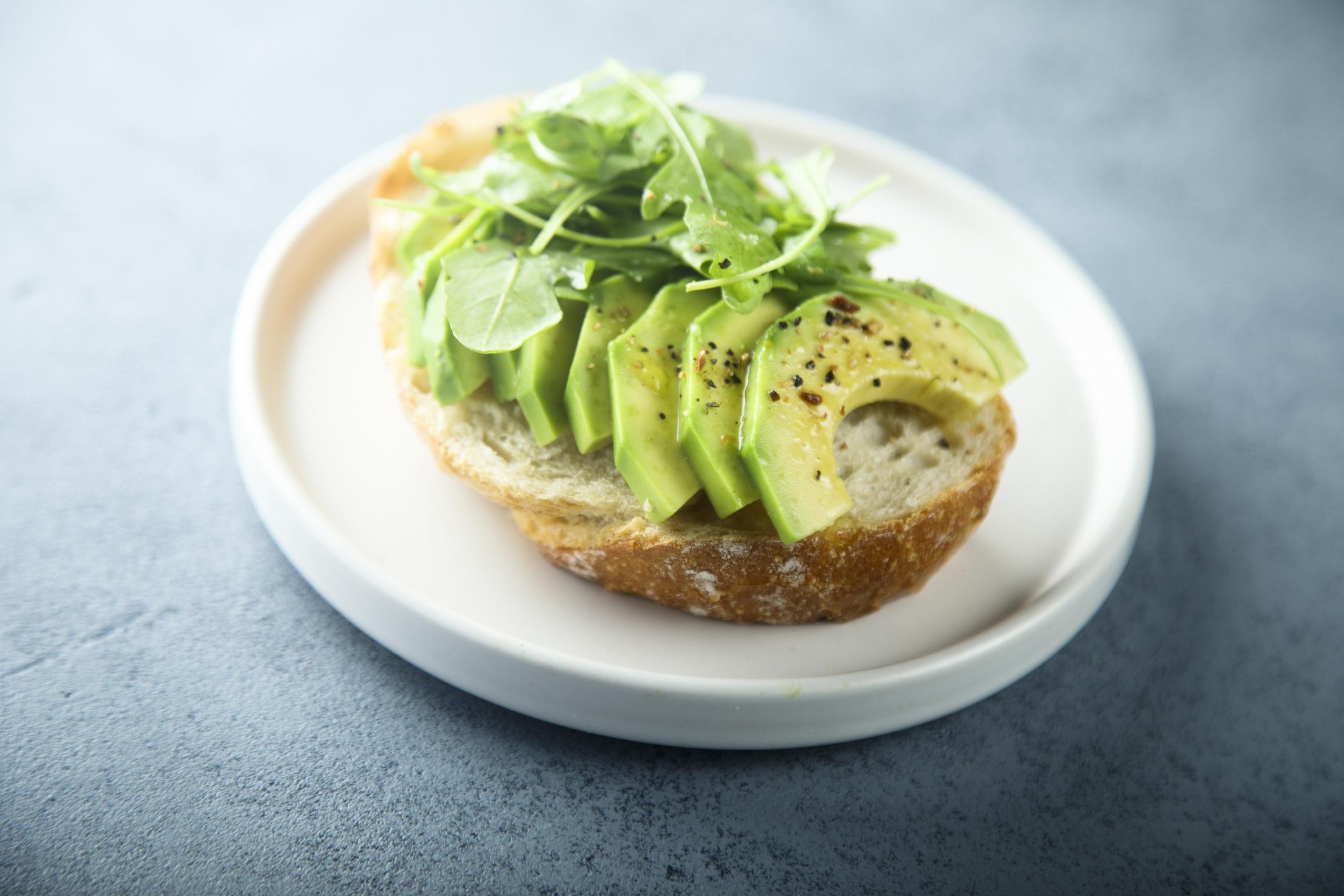 Homemade healthy avocado toast with fresh arugula