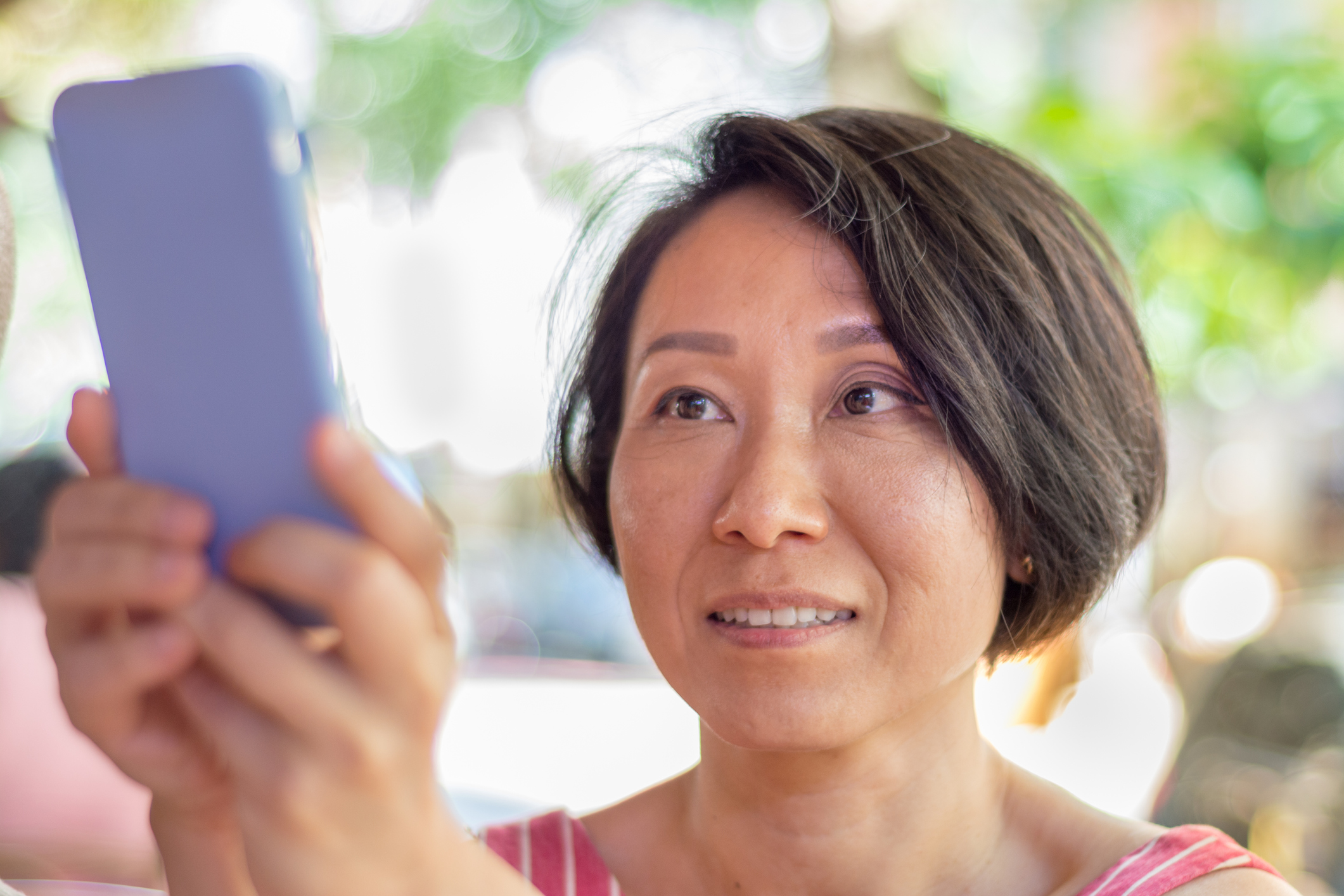 Asian mid adult woman pointing her smartphone and taking a photograph. Looking at the telephone camera app screen.