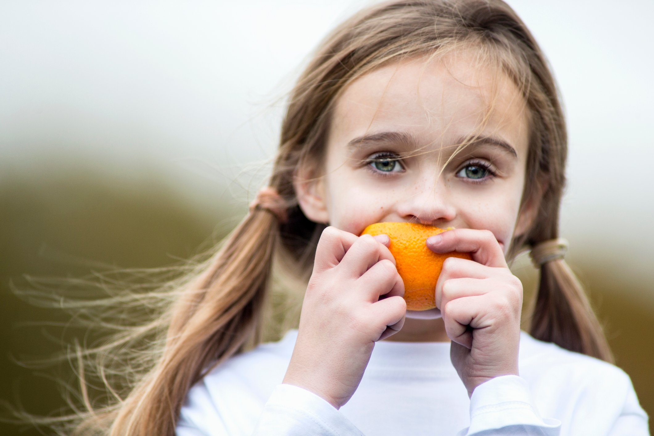 Close up of a girl eating an orange outdoors.