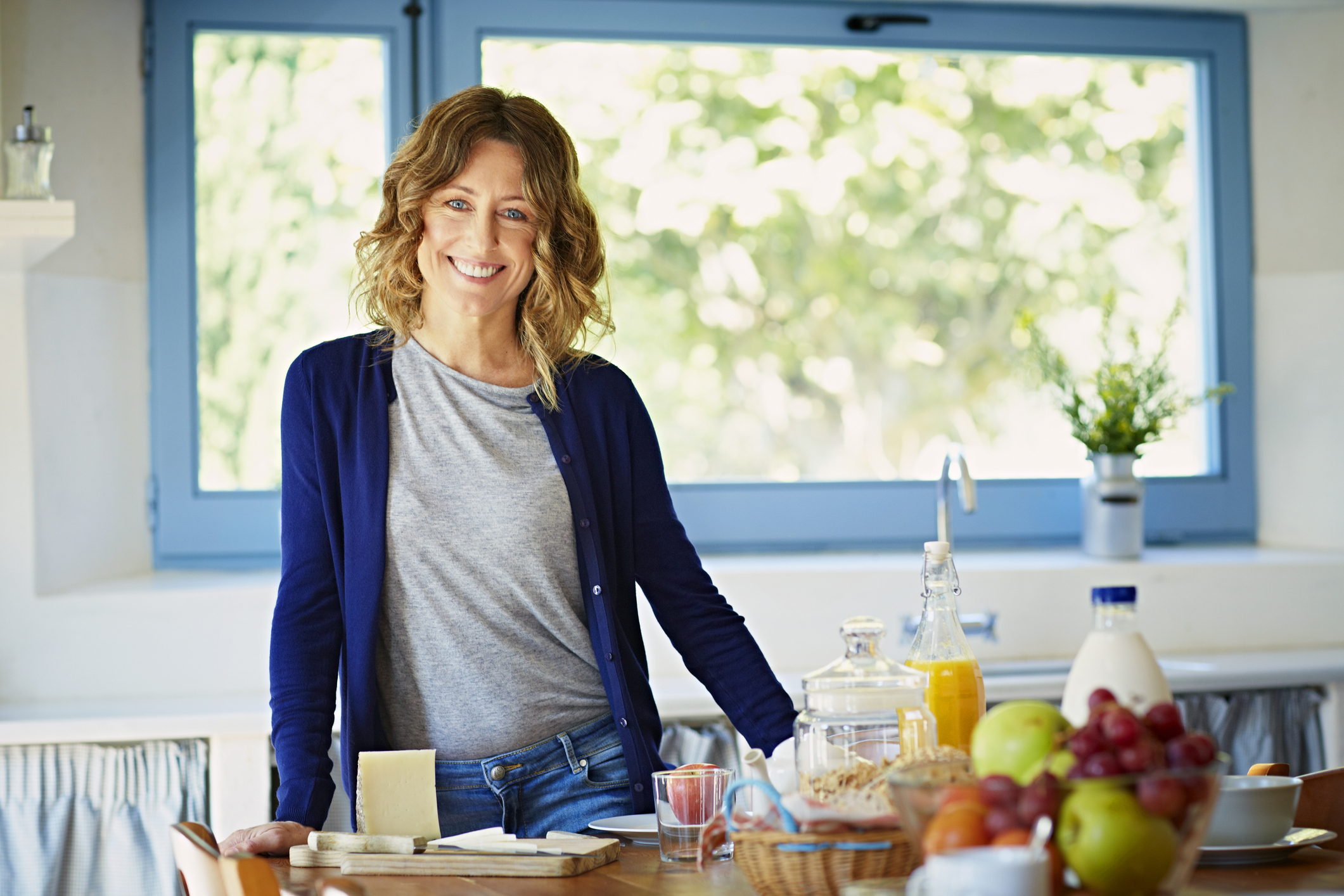 Portrait of happy woman standing at breakfast table in kitchen