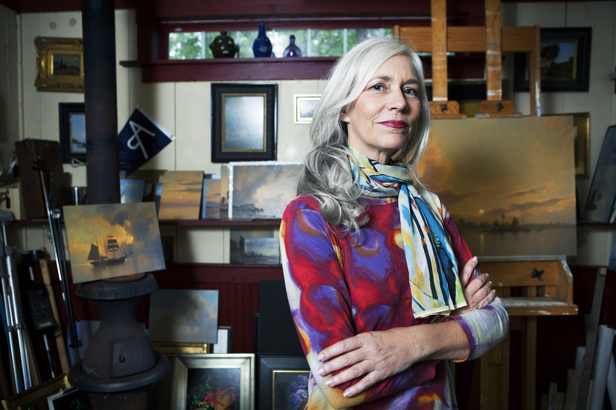 Female painter from the baby boomer generation with long, white hair posing in front of her paintings.