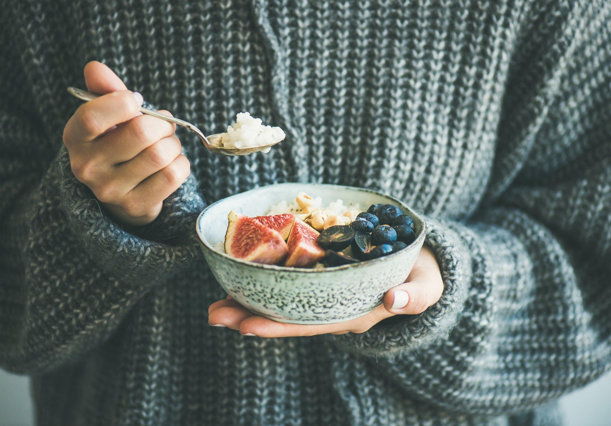 Healthy winter breakfast. Woman in woolen sweater eating rice coconut porridge with figs, berries, hazelnuts. Clean eating, vegetarian, vegan, alkiline diet food concept