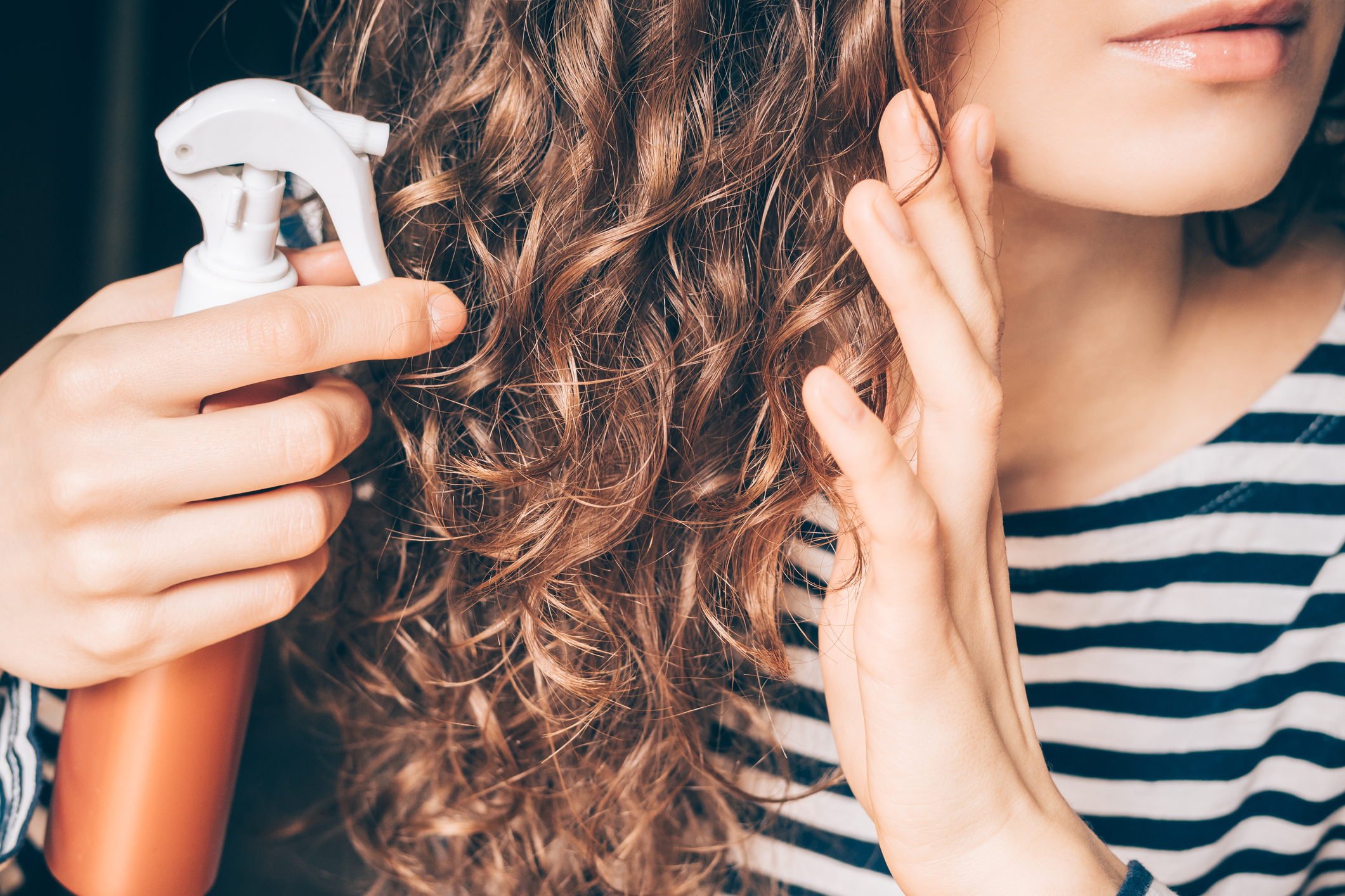 Woman applying spray on curly brown hair close-up