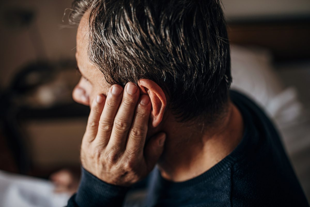 man holding ear injury