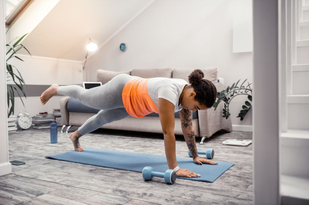 young woman doing plank pose one leg flat back