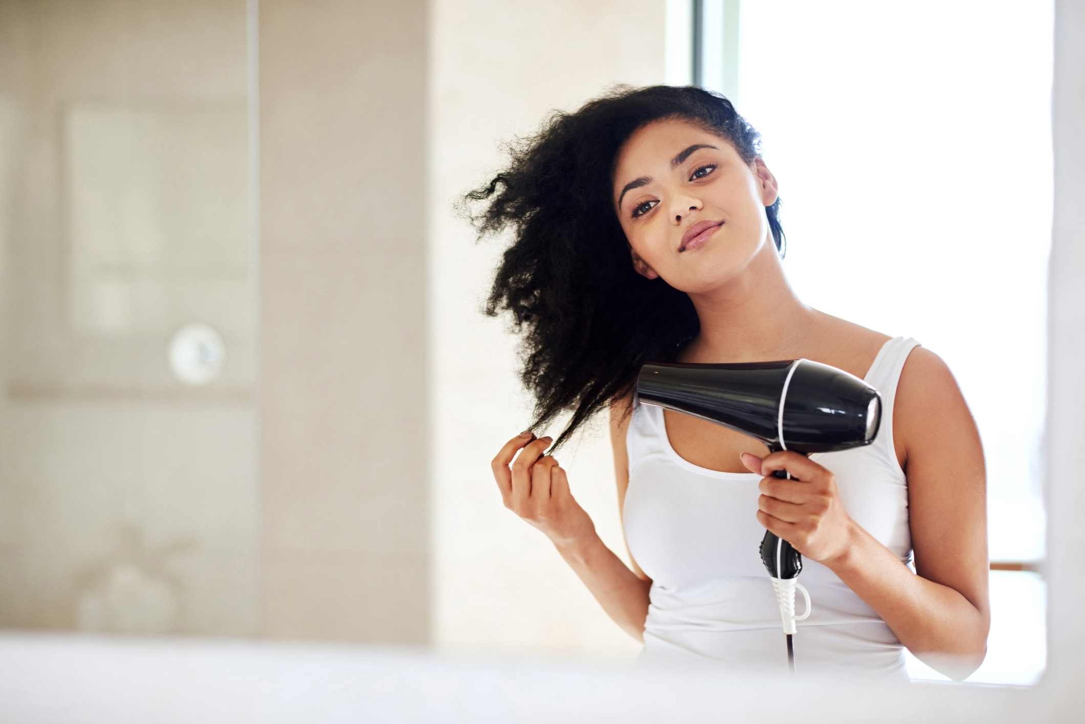 Shot of a young woman drying her hair in the bathroom