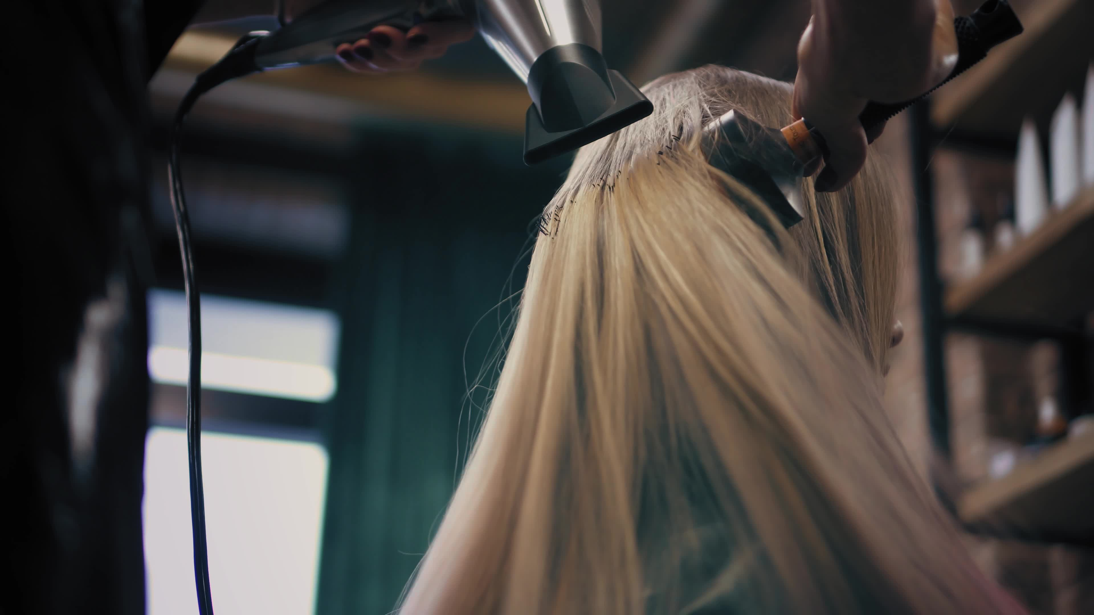 Young woman is sitting in chair in beauty salon while hairdresser dries her hair with round hair brush and hairdryer. Straightens hair. Down-up view.
