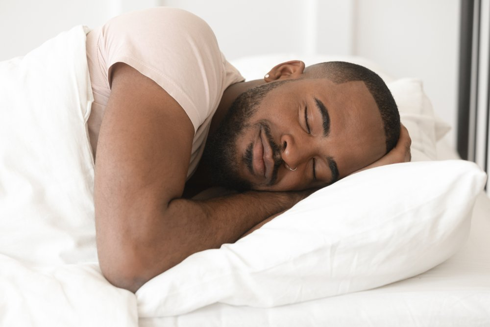 man sleeping deeply with a smile