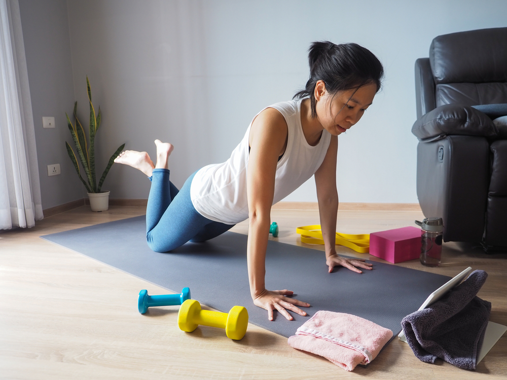 asian woman doing plank pose from knees