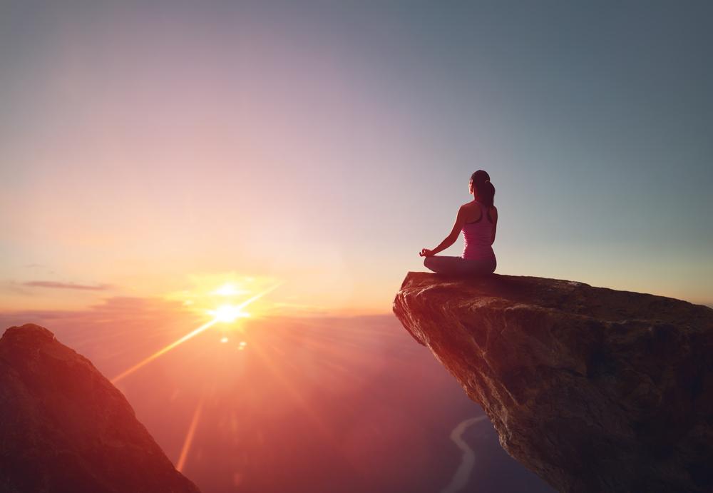 woman meditating stress relief mountaintop