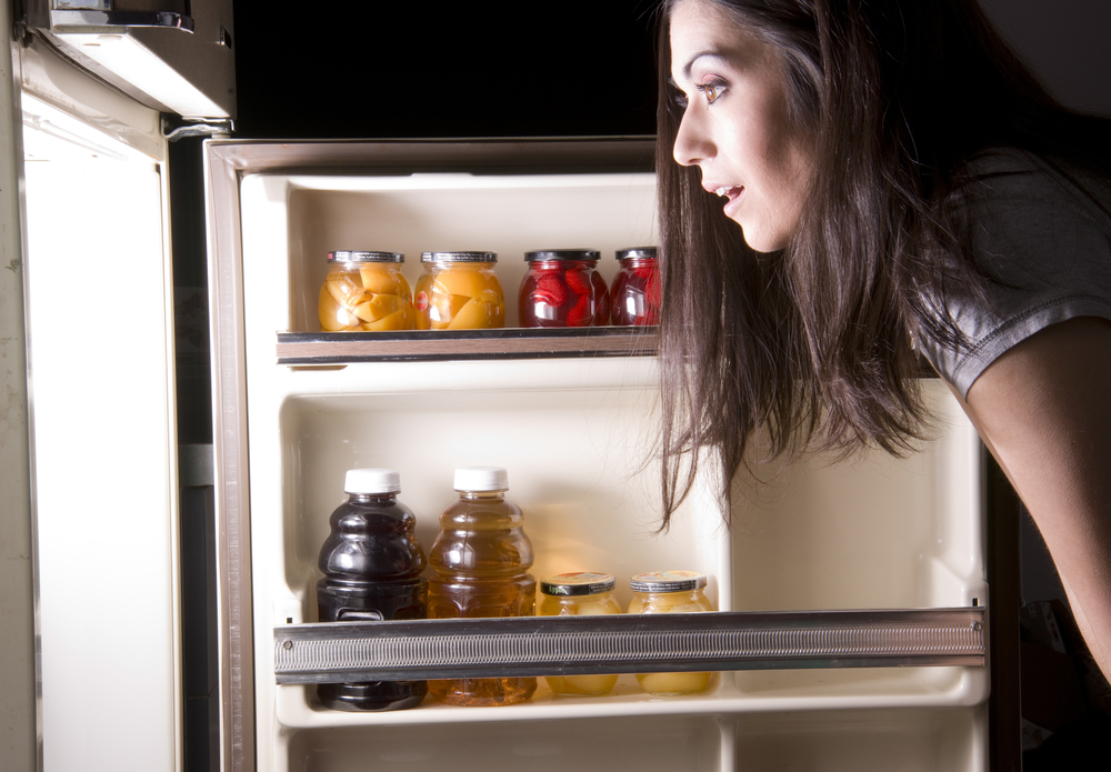 woman looking for midnight snack food in fridge