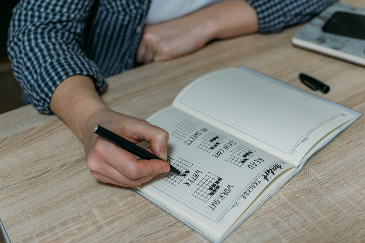 Woman writing in bullet journal.