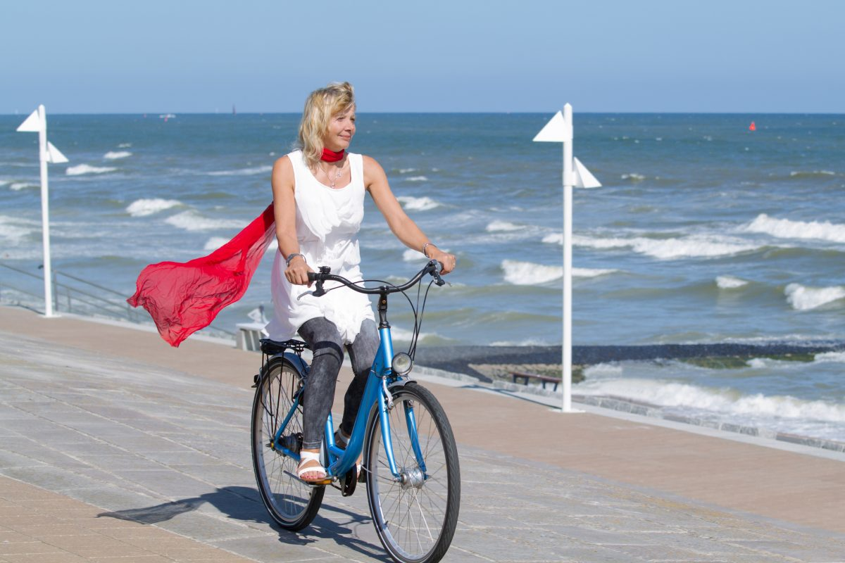 Woman riding her bike along the beach.