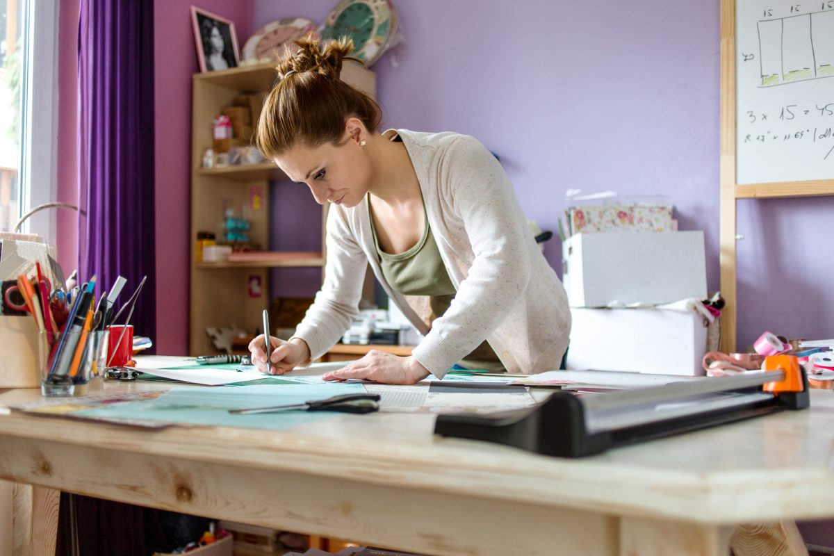 Woman adding mementos to journal page.