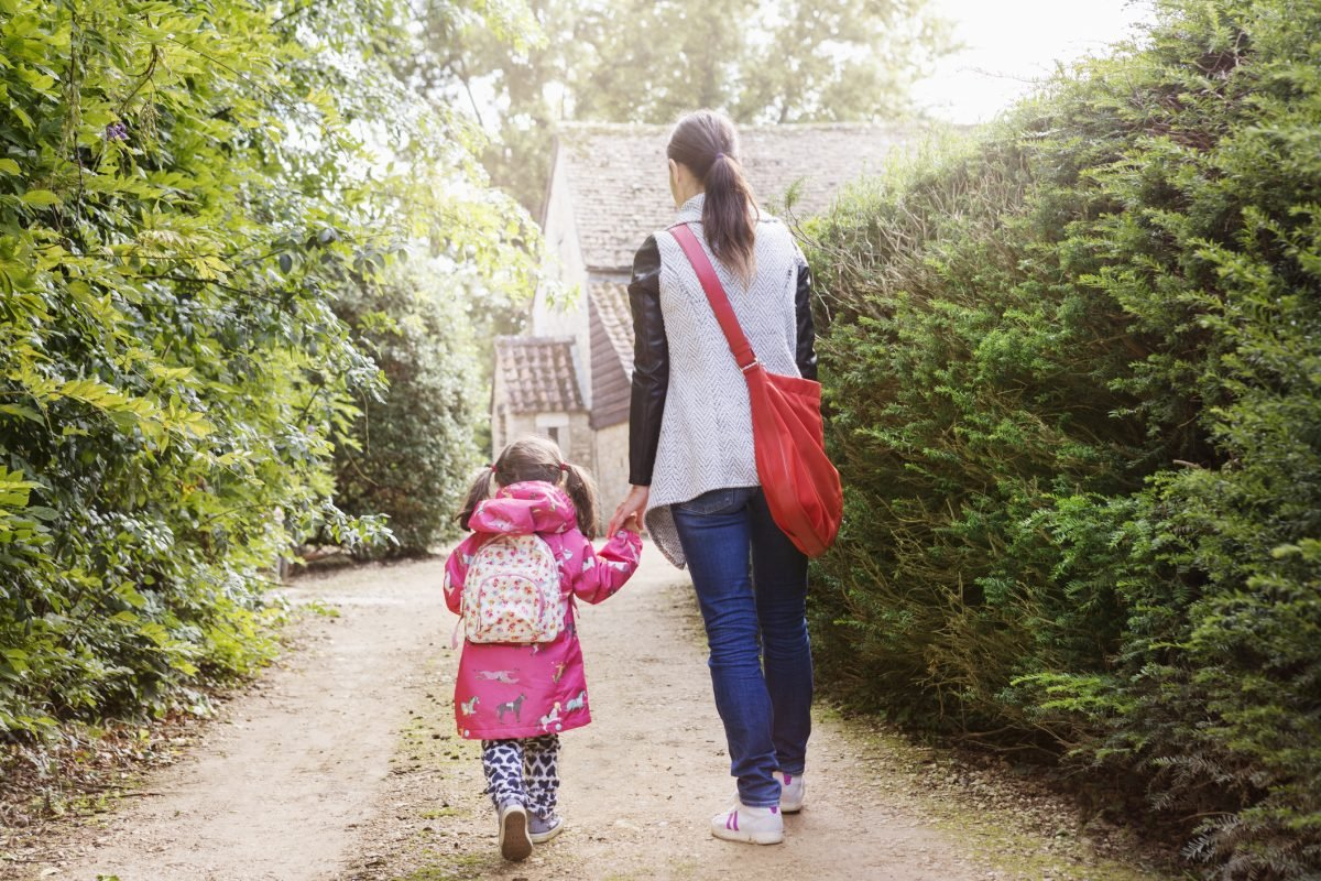Young girl walking to school with mom.