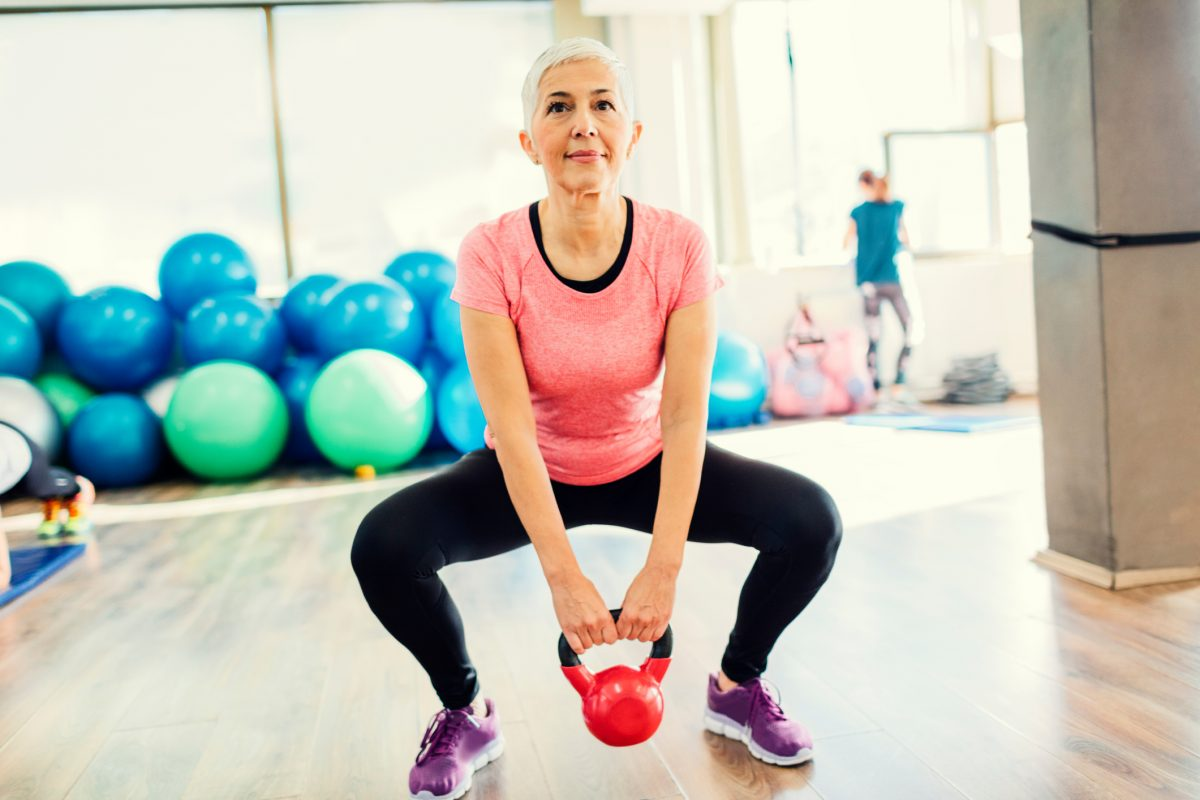 Mature woman lifting kettlebell.