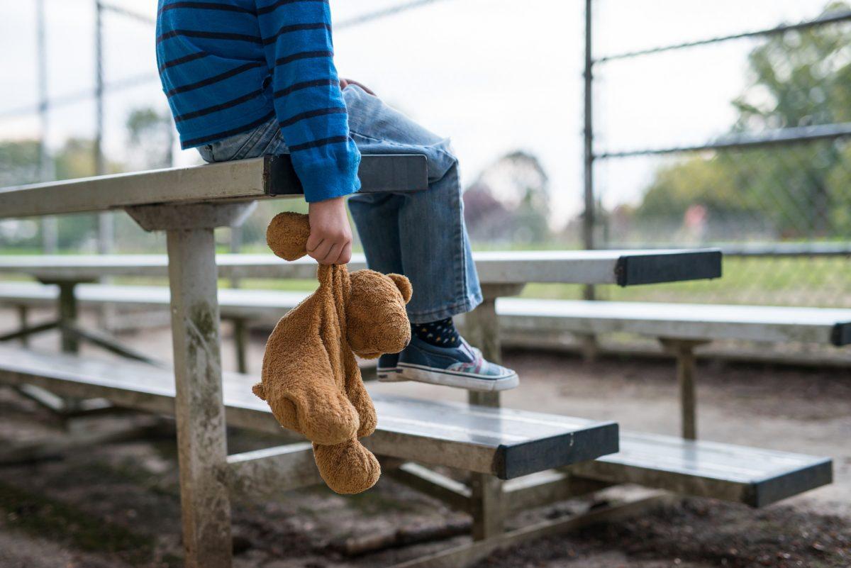 Boy sitting alone on bleachers.