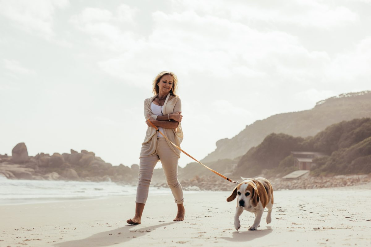 Mature woman walking dog.