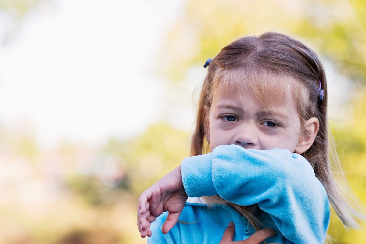 Young girl coughing.
