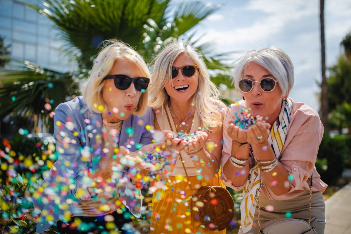 Three senior women wearing sunglasses and blowing confetti.
