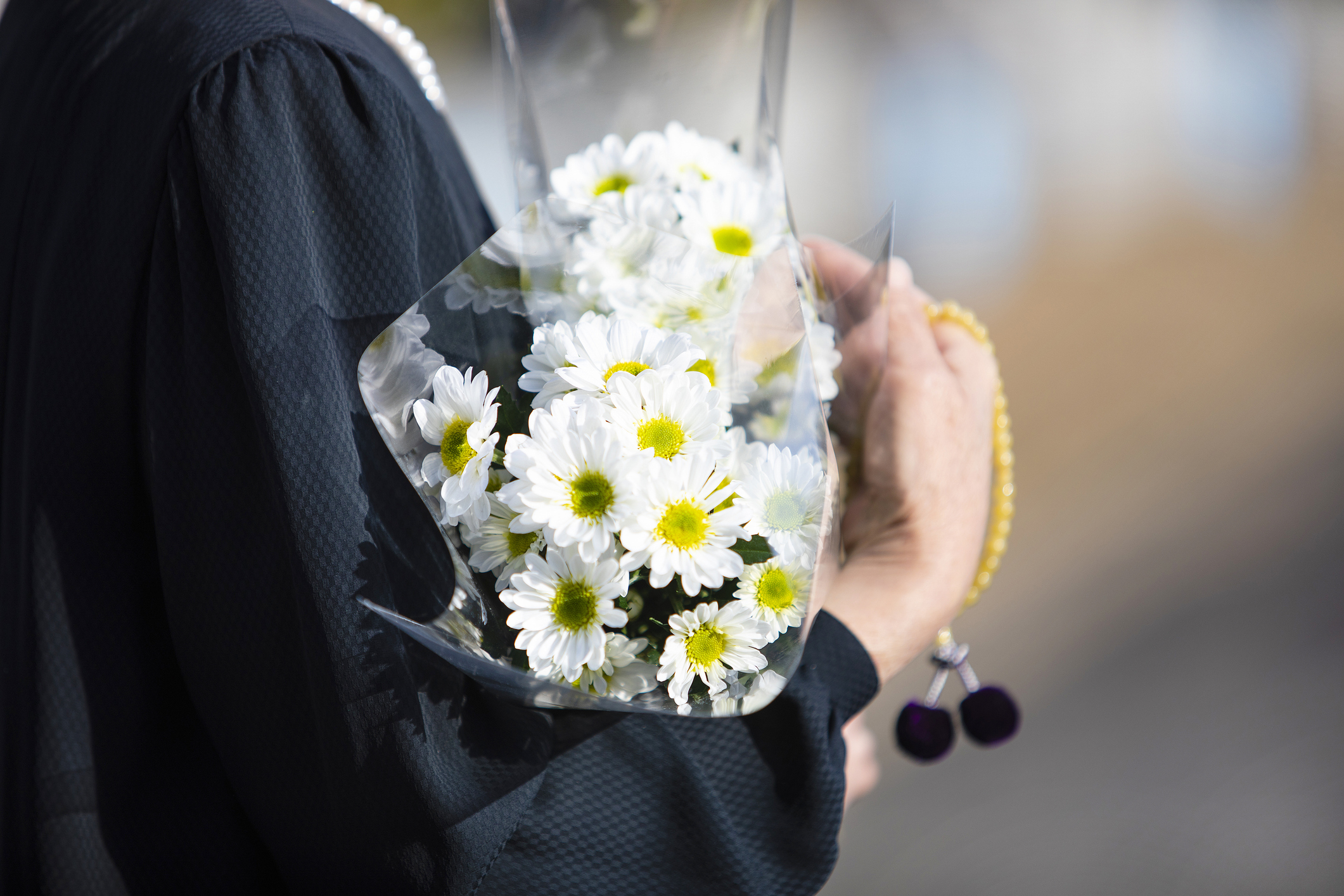An item of the ceremony of the funeral of Japan. The Japanese woman of the senior in the black mourning dress which went for a visit to a grave with a chrysanthemum bunch and beads.