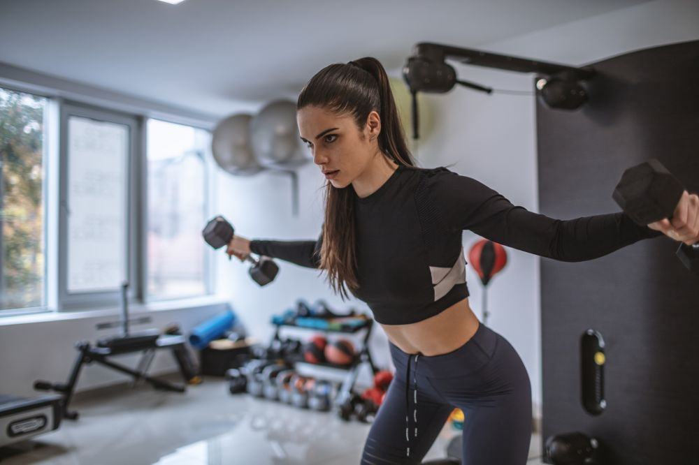 young woman doing rear fly exercise with dumbbells