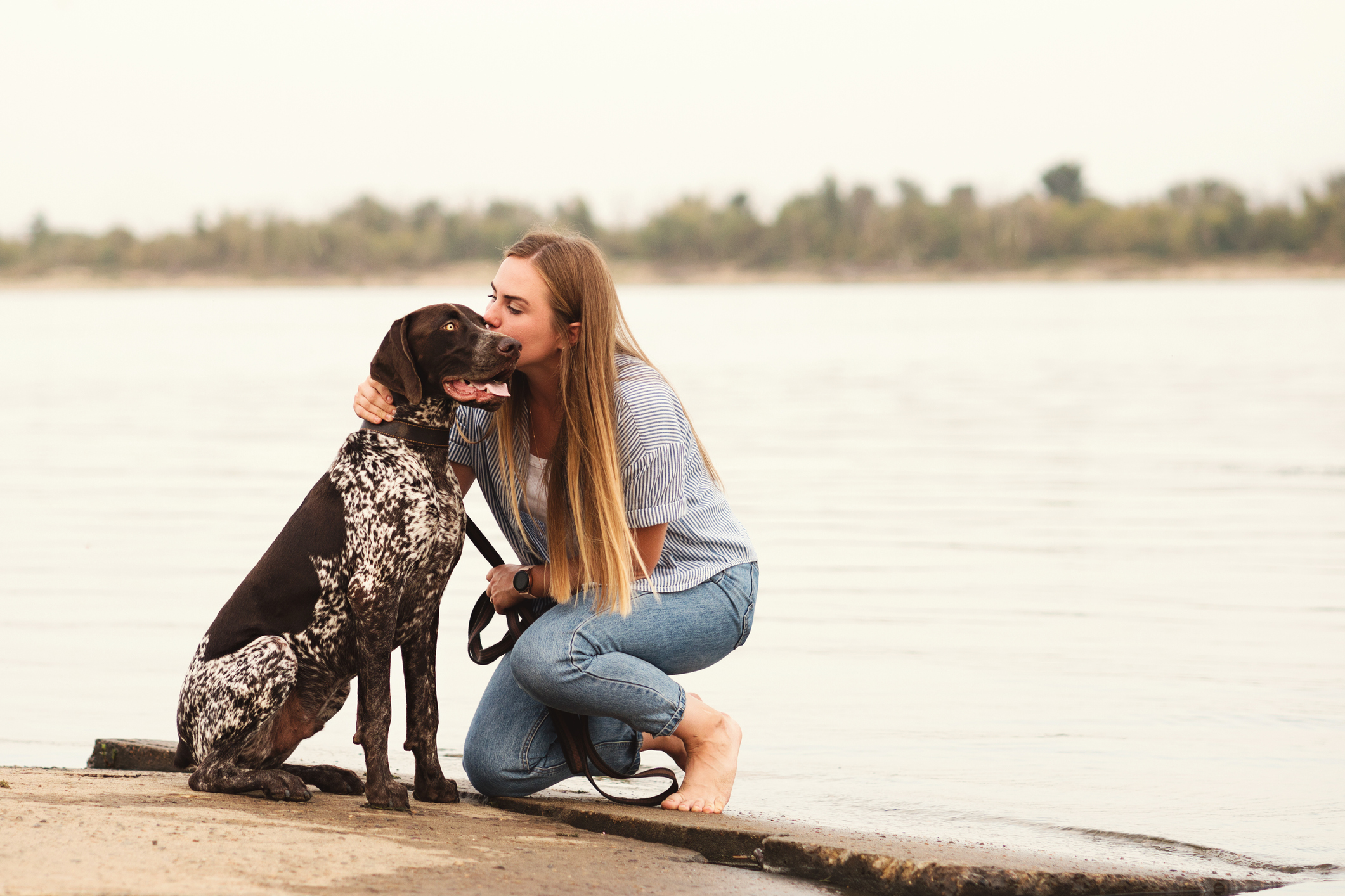 Best friends young woman and German Shorthaired Pointer sitting on by the river. Girl stroking and kissing her dog. Concepts of friendship, pets, togetherness