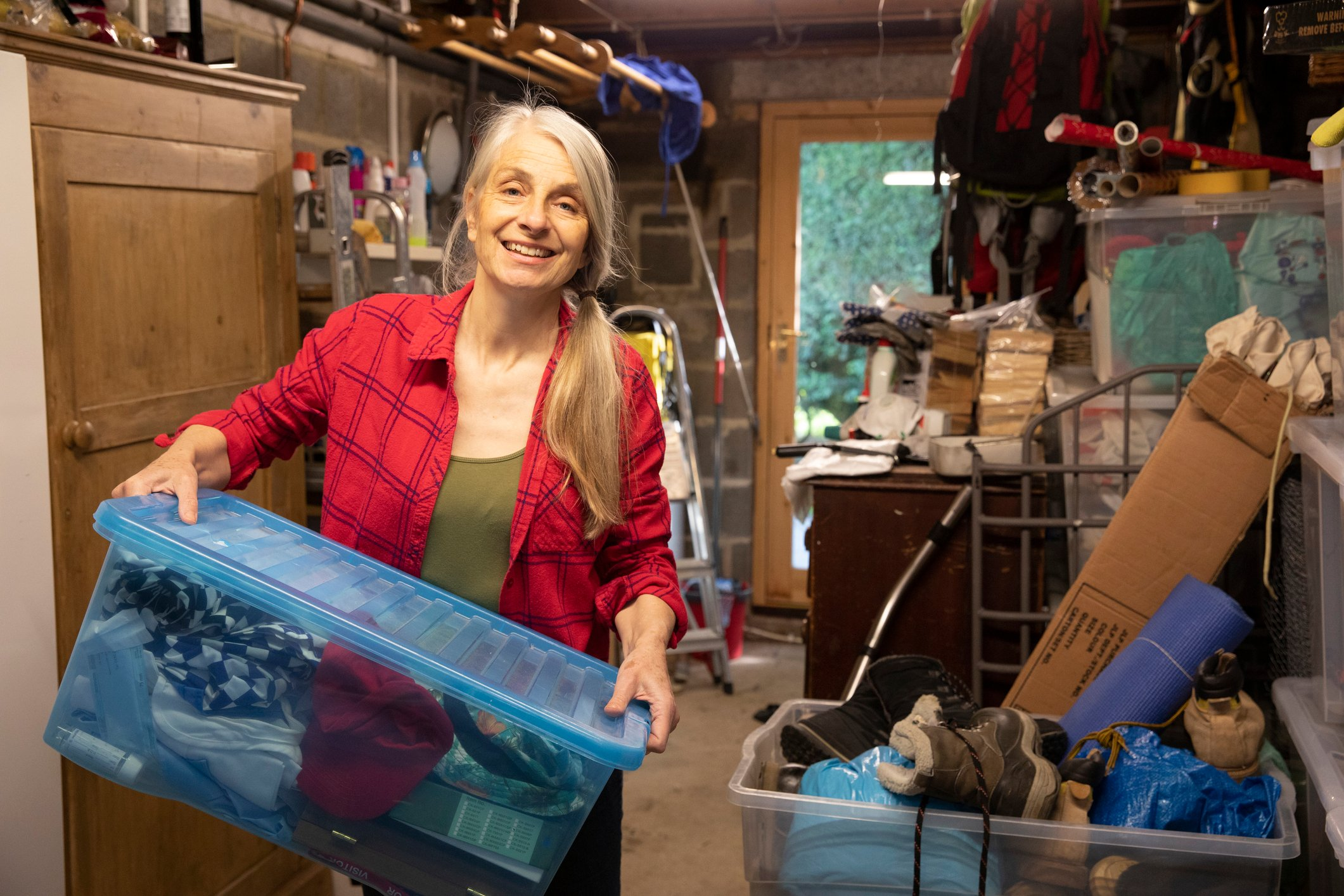 A mature woman smiles as she carries boxes of belongings to sort through whilst in lockdown at home.