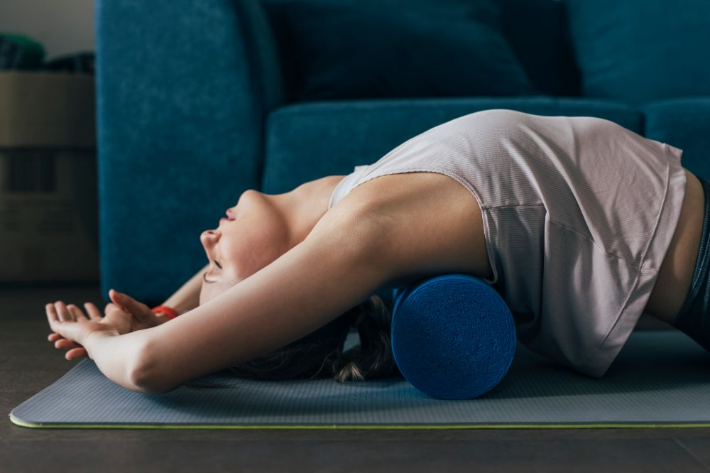 woman doing back extension stretch with foam roller