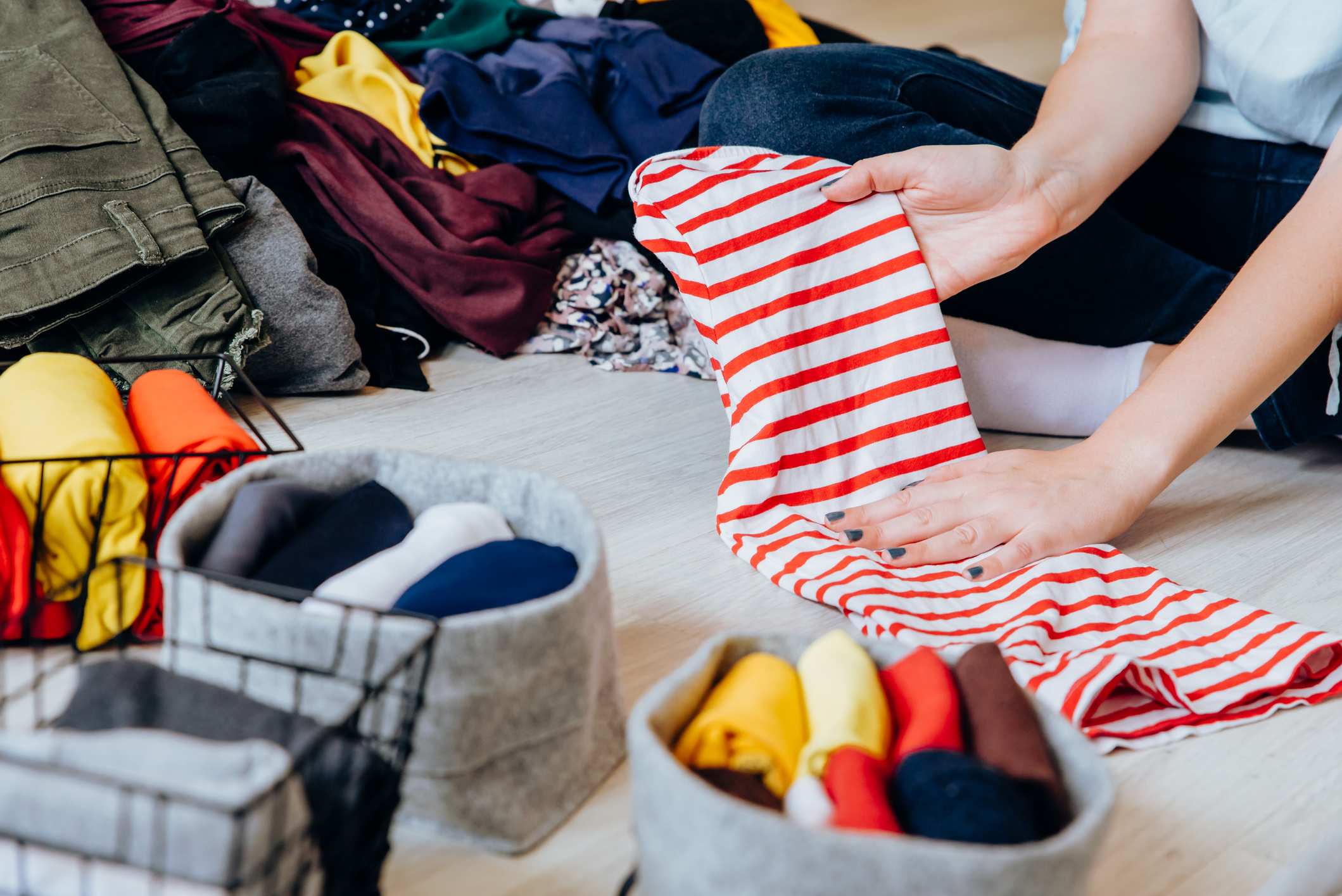 Woman folding laundry and clothes on the floor in bedroom, organizing laundry in boxes and baskets. Concept of minimalist lifestyle and japanese t shirt folding system. Konmari method