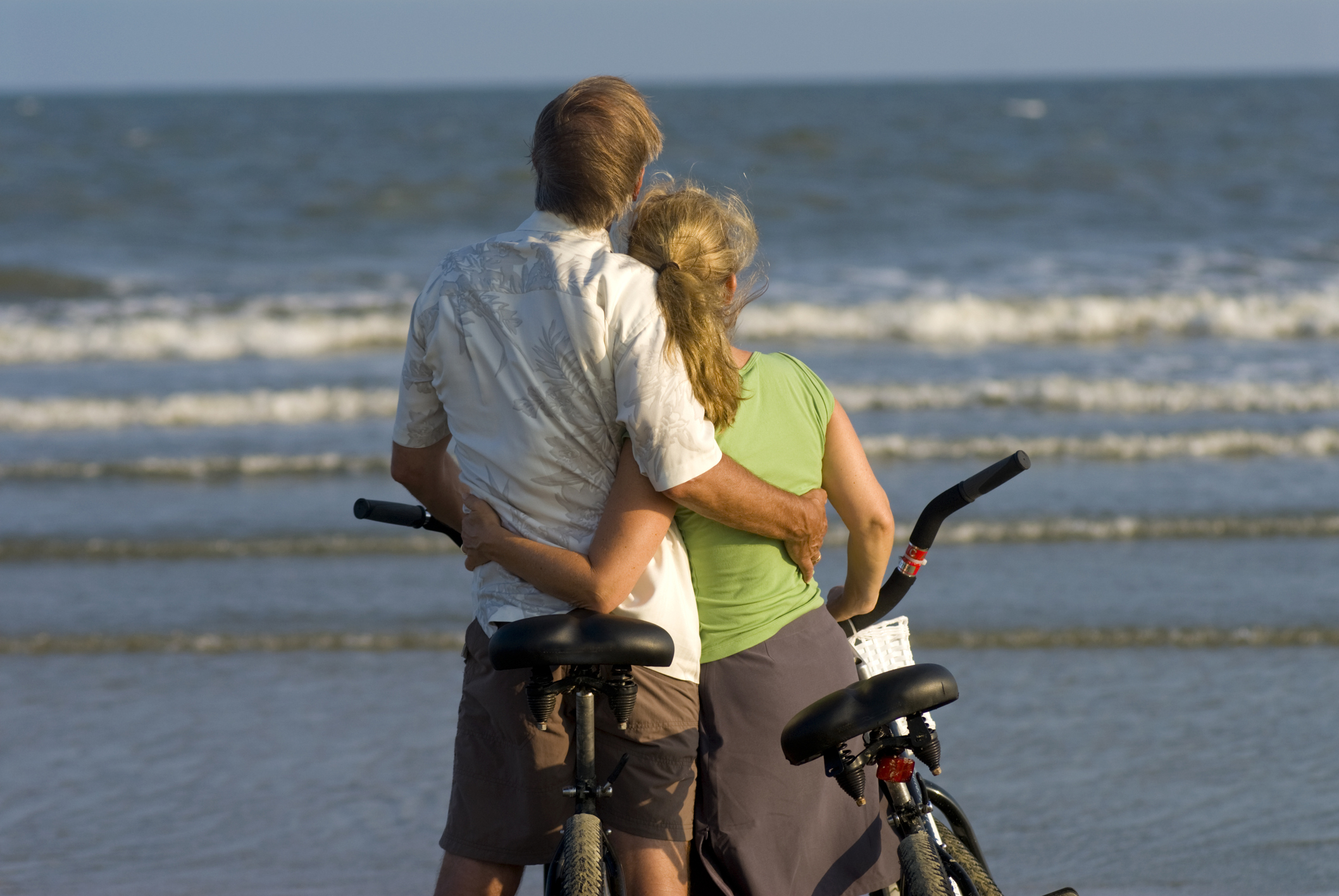 Romantic, middle aged couple at the beach with bicycles, looking into the distance