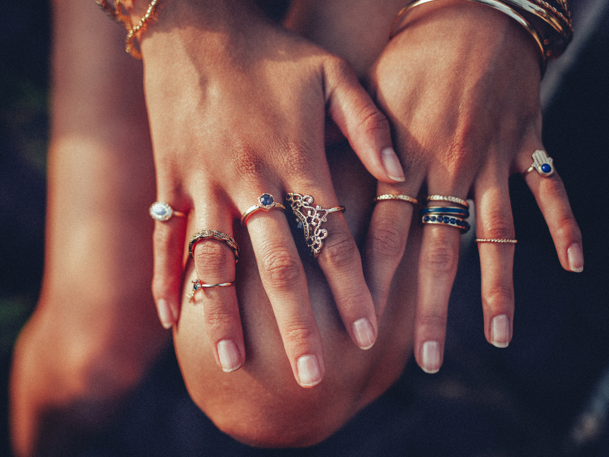 Cropped closeup of a boho girl's hands with many rings on her fingers, in gold and silver with dark blue stones