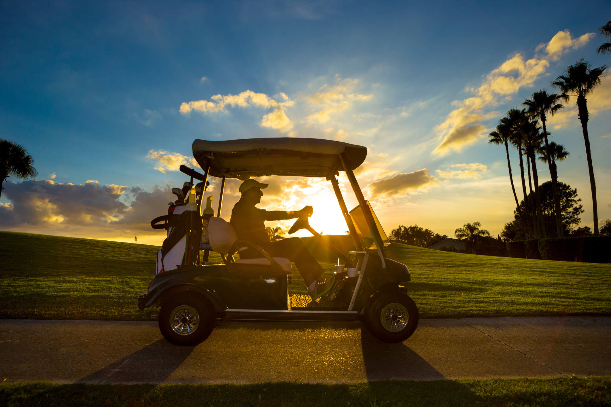 Senior man on golf course driving golf cart at sunrise