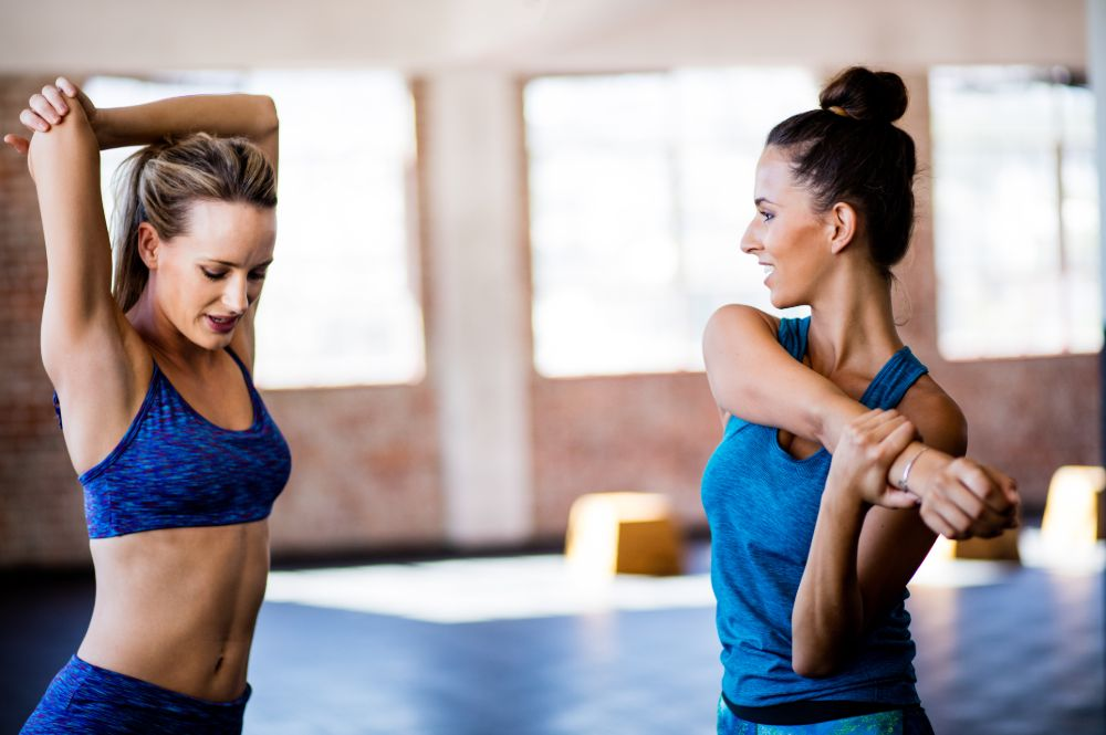 two women at a fitness studio stretching their shoulders
