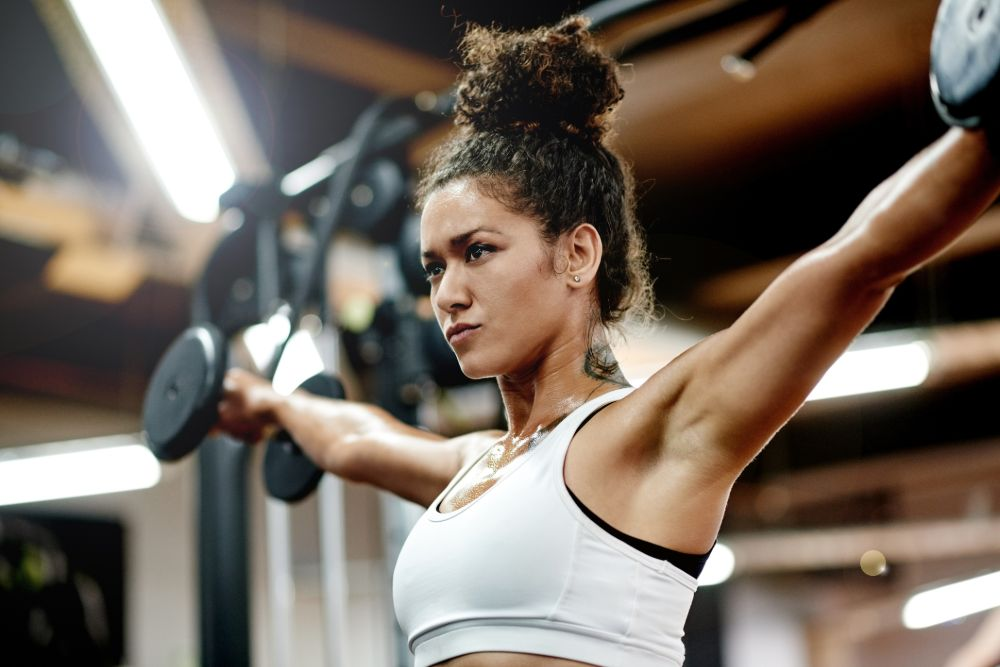 woman in gym doing lateral raise exercise with dumbbells