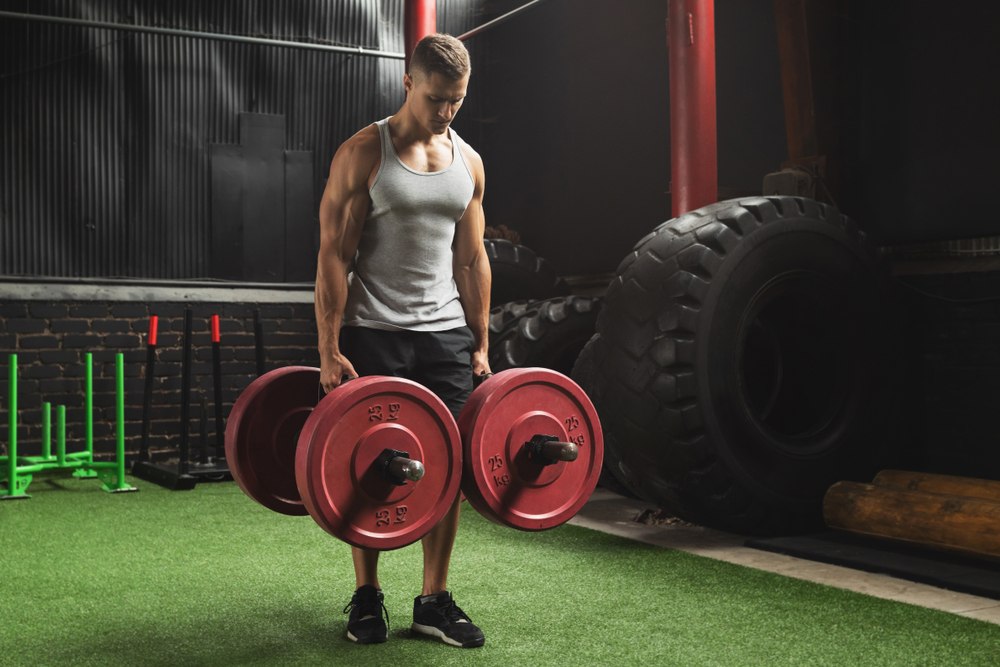 man in gym carrying heavy weights, farmer walk exercise