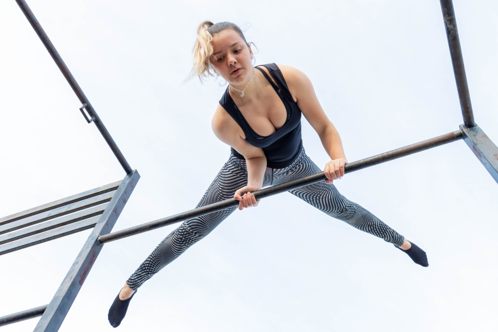woman doing body weight exercise on jungle gym