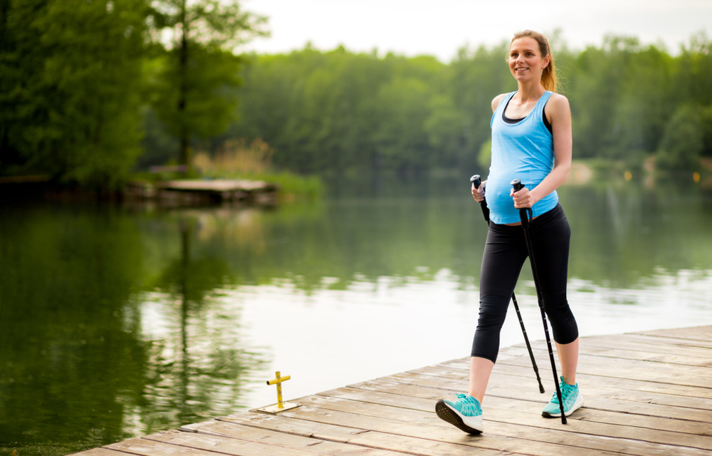 pregnant woman walking with nordic walking poles by the water