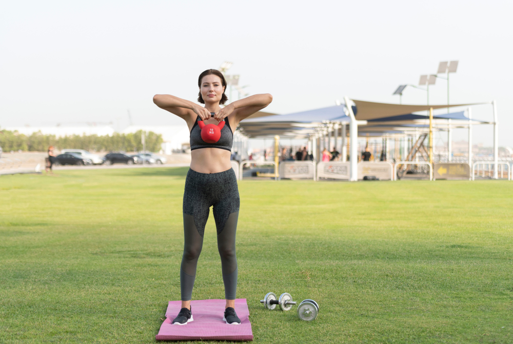 woman in park workout upright row exercise with kettlebell