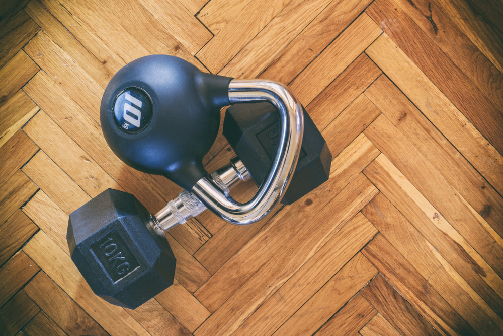 a kettlebell and a dumbbell on a wooden floor