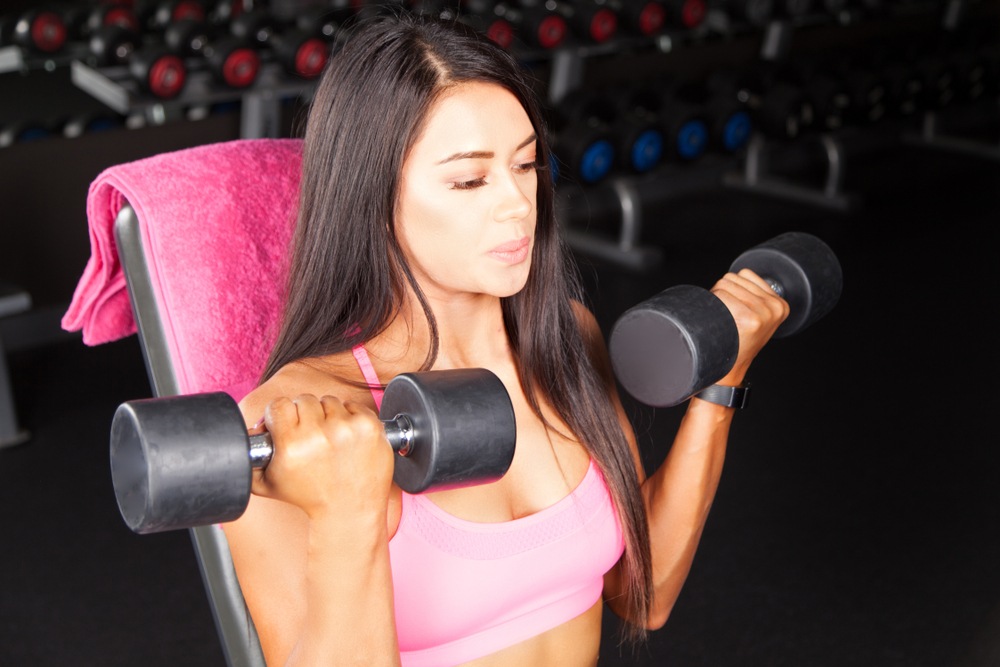 a woman in a gym doing bicep curls with dumbbells
